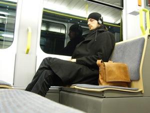 Weary man in near empty tram enjoying his trip home